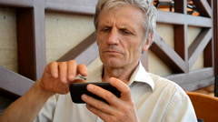 Old man with the phone close-up Stock Footage