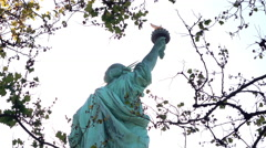 Statue of Liberty holding torch seen through trees 4k Stock Footage