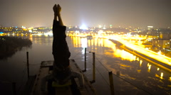 Strong man making headstand on the bridge at nighttime, self-control, balance Stock Footage