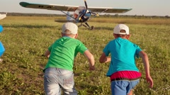 Two kids running to the airplane Stock Footage