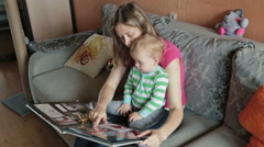 Mother watching with her son photo album - stock footage