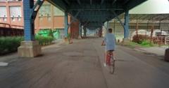 Following Biker Under Bridge in City Industrial Area Stock Footage