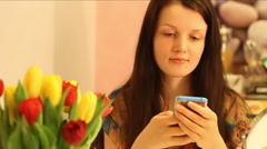 Beautiful young girl with a bunch of tulips is texting Stock Footage