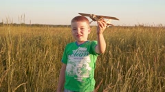 Naughty boy in wheat field running with a toy plane Stock Footage