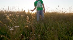 Boy in wheat field running toward with a toy plane Stock Footage