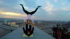 Dangerous stunts by professional athletes on top of high bridge, acro yoga poses Stock Footage