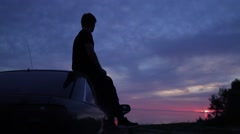Man sitting on a car and then walking on beach Stock Footage