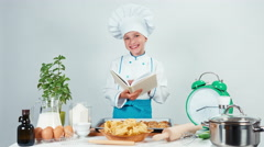 Little chef cook holding book of recipes and smiling at camera - stock footage