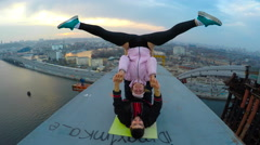 Smiling man and woman doing acrobatic yoga stunts on bridge, adrenaline junkies Stock Footage