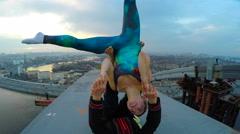 Two athletes doing acro yoga exercises on bridge, risky hobby, extreme sports Stock Footage