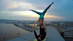 Man and woman practicing acrobatic yoga on top of bridge, dangerous sports Stock Footage
