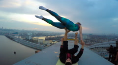 Young couple enjoying adrenaline from acrobatic yoga on top of high bridge Stock Footage