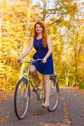 Girl in dress on bike. Stock Photos