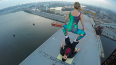 Extreme sport, female balancing on male legs on top of bridge, dangerous hobby Stock Footage