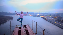Brave young woman standing in yoga pose on the top of bridge, dangerous hobby Stock Footage