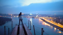 Happy man standing on top of bridge and pointing at beautiful view on night city Stock Footage