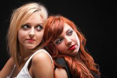 Two happy young girlfriends black background Stock Photos