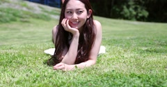 Attractive smiling young Japanese woman laying on grass in a white dress Stock Footage