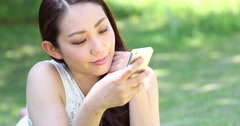 Attractive smiling young Japanese woman using smartphone on grass Stock Footage