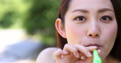 Attractive young Japanese woman blowing soap bubbles in a city park Stock Footage