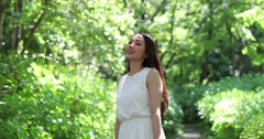 Portrait of attractive young Japanese woman in a white dress in a green forest Stock Footage