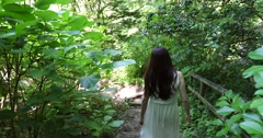 Attractive young Japanese woman walking in a green forest wearing a white dress Stock Footage