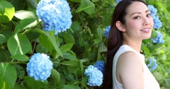 Portrait of attractive young Japanese woman with blue hydrangea flowers Stock Footage