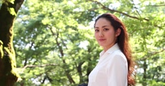 Portrait of attractive young Japanese woman in a white shirt in a city park Stock Footage