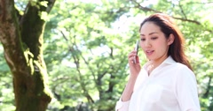 Attractive young Japanese woman in a white shirt on the phone in a city park Stock Footage