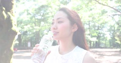 Attractive young Japanese woman drinking water in a city park Stock Footage