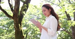 Attractive young Japanese woman in a white shirt using  her tablet in a city Stock Footage