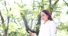 Attractive young Japanese woman in a white shirt taking selfie in a city park Stock Footage