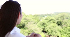 Portrait of attractive young Japanese woman in a white shirt at a city park Stock Footage