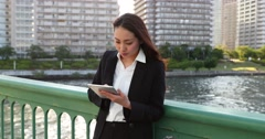 Attractive young Japanese woman in formal clothes using tablet by a river Stock Footage