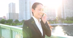 Attractive young Japanese woman in formal clothes walking while talking Stock Footage