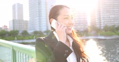 Attractive young Japanese woman in formal clothes walking while talking on the Stock Footage