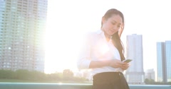 Attractive young Japanese woman in formal clothes using smartphone by a river Stock Footage