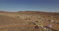 Tracking shot of rubbish in arid landscape, Erg Chebbi, Morocco Stock Footage