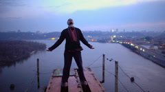 Young man standing on top of bridge, looking for sense of life, danger, freedom Stock Footage