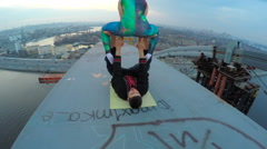 Man holding woman on top of bridge, acrobatic yoga at great height, adrenaline Stock Footage