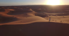 Drone footage of woman standing on sand dune at Erg Chebbi, Morocco Stock Footage