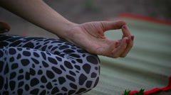 A beautiful young lady sitting on a green field in a lotus pose Stock Footage