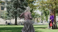 A woman hula-hooping in the park Stock Footage