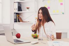 Woman has healthy business lunch in modern office interior Stock Photos