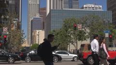 Pedestrian people cross busy road in Los Angeles financial area tall building LA Stock Footage