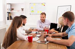Business meeting. Young hipsters businessmen and women at modern office Stock Photos