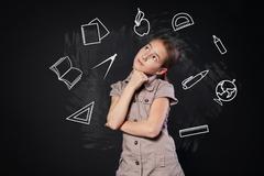 Small girl near chalkboard think of school subjects Stock Photos