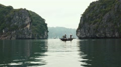 Fishermen and limestone mountains, Ha Long Bay Vietnam. Long shot, telephoto. Stock Footage