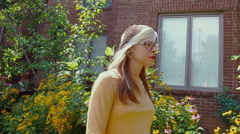 alternative woman walking outside summer garden - stock footage