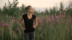 Beautiful young healthy woman standing at a green field and looking away - stock footage